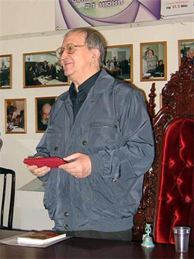 upper body of man with glasses in shirt and jacket holding an object in front with both hands