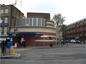 A brown- and tan-tiled building with a blue sign reading
