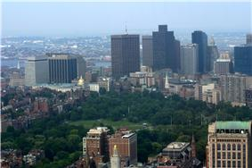 City skyline with a body of water in the background and a green park in the foreground