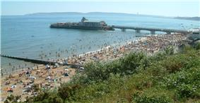 photograph of a crowded Bournemouth beach, near Bournemouth pier, on a hot summer's day