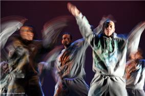 A close-up shot of a dance performance by five male hip-hop dancers in gray sweatsuits.