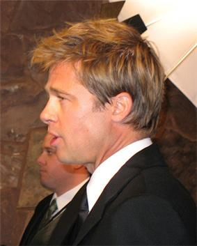 A side view of a man, who is facing to the left, with light brown hair. He is wearing a black suit and tie with a white shirt. Another male, also wearing a suit, is visible in the background.