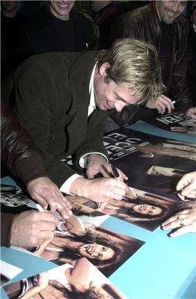 A Caucasian male bent over a table autographing a movie poster. He has light brown hair with blonde highlights, and is wearing a dark-colored trench coat with a white shirt. Visible in the background and foreground are other people, some of whom are also signing autographs.
