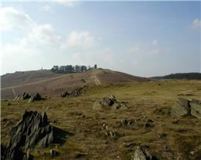 Picture of Old John Tower and the War memorial, at the top of the hill, above jagged rocks.