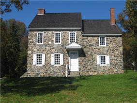 A two-story fieldstone house</center>