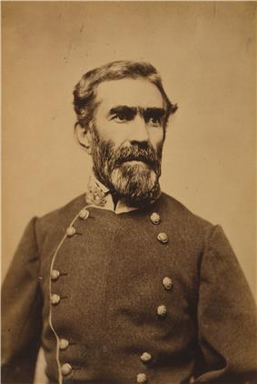 A man with dark wavy hair and a mustache and beard, wearing a military uniform