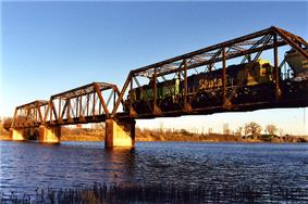 A train crosses a bridge over a wide river.