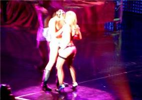 Image of two people kissing. In the left, the man wears underwear and boots. In the right, the blond woman wears lingerie, stockings and high heels.