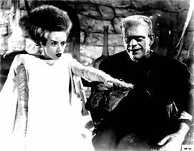 The Bride of Frankenstein has black hair with a white streak running through it, is dressed in a white gown, and has a blank expression. She is standing on the left with her left hand elevated. On the right is Frankenstein's monster, standing on the right and smiling. His right hand is below hers. The background includes walls made of stone.