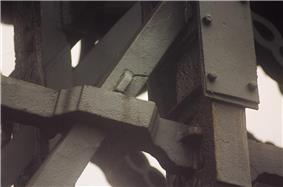Iron members of the bridge, one showing a visible crack and one repaired by steel sandwich plates bolted around it