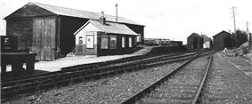 small wooden hut with a large wooden shed behind it. In front of the hut is a platform at two different heights, and in front of the platform are two sets of railway tracks. The tracks lead into a further pair of wooden sheds.