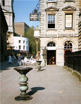 Two ornate metal pillars with large dishes on top in a paved street, with an eighteenth-century stone building behind, upon which can be seen the words