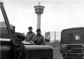 Two British soldiers carrying rifles standing behind a pair of Land-Rover vehicles, one of which has a