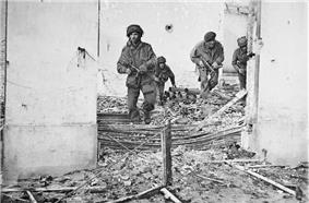 Four men in bombed building walking over rubble