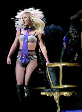 Image of a blond female performer. She has a headset around her hand and is wearing sparkly silver and black lingerie, fishnet stockings and knee-high black boots. She stands in front of a black and golden couch.