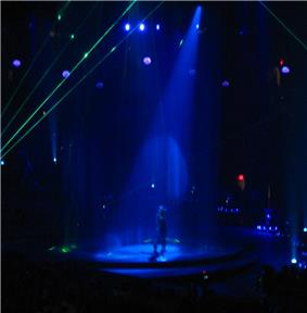 Faraway image of a female performer. She is walking through a water screen that is falling from the ceiling. A blue spotlight is on her. She is wearing blue jeans and a plastic cowboy hat. Green laser lights surround the stage.