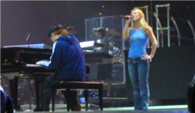Image of a blond female performer. She is wearing blue jeans and a sleeveless light blue top. She is standing next to a piano player, who is playing a big black piano. Her left hand is in her hip while her right hand holds her mic while she is singing. Two members of the crew stand a few meters behind them.
