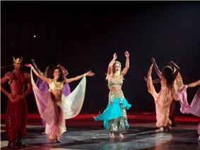 A blond female performer. She is wearing a Bollywood-inspired outfit, while surrounded by a group of dancers.