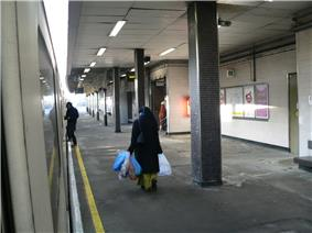 Three people walking on a platform, the one on the left boarding a train, the one in the middle carrying bags, and the one on the right walking through a door