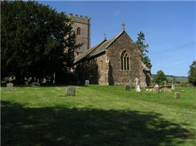 Stone building with square tower, partially obscured by trees. In the foreground are gravestones.