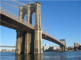 A below view of a large suspension bridge over a river connecting to an area covered with tall buildings. Another bridge and other buildings can be seen in the background.