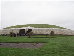 A large, circular stone tomb with a top covered with a thin grass.