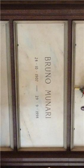 A white marble gravestone on the wall of a chapel, with only the name and dates of birth and death inscribed