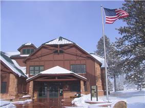 Two story wood building next to flag pole with U.S. flag waving in the wind. Snow on ground.