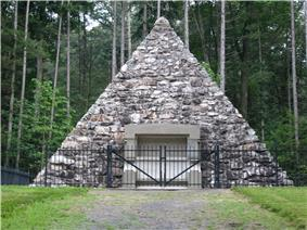 A fieldstone pyramid surrounded by a fence with pine trees in the background