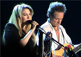 A blonde, female singer and a male acoustic guitarist are performing together in concert.