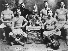 A black-and-white image of young male basketball players dressed in team uniform, sitting around a display that holds trophies. The plaque below the display reads