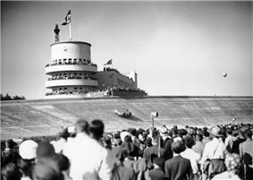 A large crowd of people watch a streamlined single-seater drive around a massive curved racing bank. A Nazi flag is flying in the distance atop a tower.