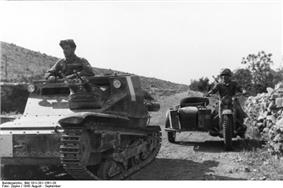 A small tank, with a motorbike and rider to the right, move towards the camera.