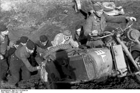 a black and white photograph of a group of soldiers pushing a motorcycle combination up a hill, p. 244.