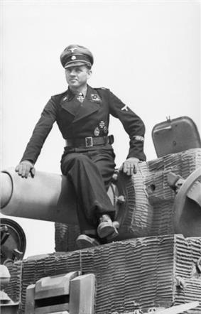 A man, wearing dress uniform and a cap, sits on top of a tank barrel; the tank is not fully in view.