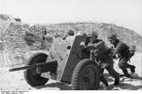 a black and white photograph of soldiers pushing a light artillery piece
