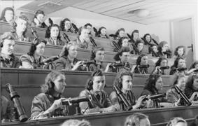 A group of young women, wearing headsets, sitting in an auditorium, controlling projectors.
