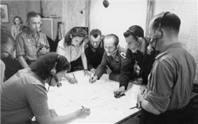 Black-and-white photograph of men and women wearing headsets standing around a table and making notes on a large map.