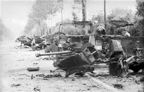 Several destroyed vehicles line the side of a tree and hedge lined road. A destroyed gun, twisted metal and debris occupy the foreground.