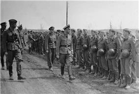 a black and white photograph of a bespectacled Heinrich Himmler in uniform walking along a line of soldiers in Waffen-SS uniform