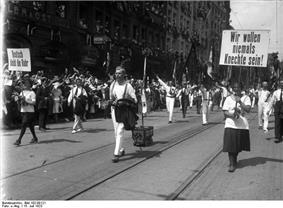 People holding banners and waving flags march down a street. Lining the road are crowds of supporting people.