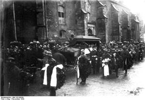 Photograph of Scheer's funeral procession; the horse-drawn hearse is accompanied by an honor guard