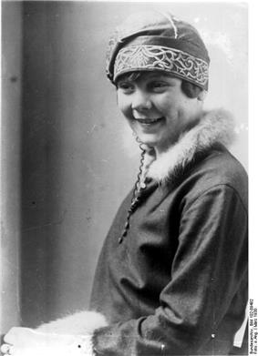 A young smiling woman wearing an embroidered hat and a jacket with furred collar and sleeve hems.