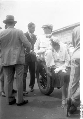 Caracciola sits on what appears to be the back of a vehicle. A young woman sits in front of him.