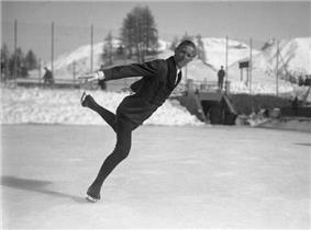 A male figure skater looks at the camera while performing a figure skating element on an outdoor ice rink.