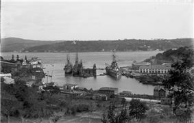 A large warship is tied to the dock in a narrow channel of water.