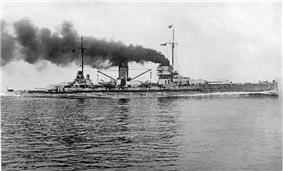 A large warship plows through the water, thick black smoke pouring from its two central smoke stacks.