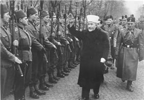 a man wearing Muslim mufti clothing holding his hand up in salute as he and a group of SS officers inspect a line of soldiers