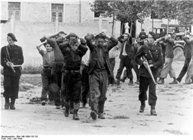 Captured men, with hands behind their heads
