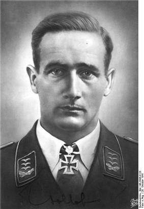 The head a man, shown from the front. He wears a military uniform, a white shirt with an Iron Cross displayed at the front of his shirt collar. His hair appears dark and is combed back, his facial expression is a determined; his eyes are looking into the camera.